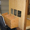 "It's easier to temporarily attach one side at a time, complete it, then remove it while working on the next side. Otherwise you're sitting inside the coop making connections. Here you see the nesting boxes waiting to be attached to the side. <br /> The plans called for one cutout for the nesting boxes, but leaving a strip of wood in between gives a more secure attachment and should make the boxes ""feel"" more separate from the inside of the coop.<br /> The height of the nesting boxes is based on a comfortable height for Kathy to reach in for eggs. The whole coop is higher than the plans so our small wheelbarrow will fit under the frame and make cleaning easier."