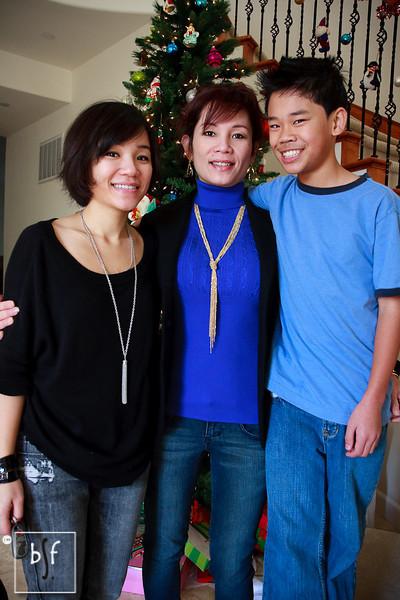 Ly, Dung, and Andrew on Christmas Day. Andrew has grown quite a bit in the last few months, but he isn't taller than his mom just yet! Andrew is standing on stairs.