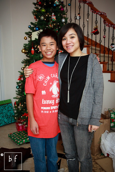"""Andrew and Ly. Ly got Andrew a funny Vietnamese spicy chili sauce t-shirt for Christmas. """"20% Less MSG. Shake first."""" :-)"""
