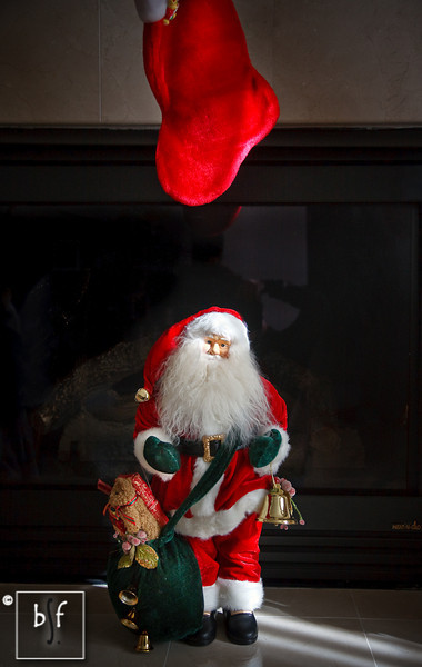 Santa came down the chimney and stood underneath Andrew's stocking.