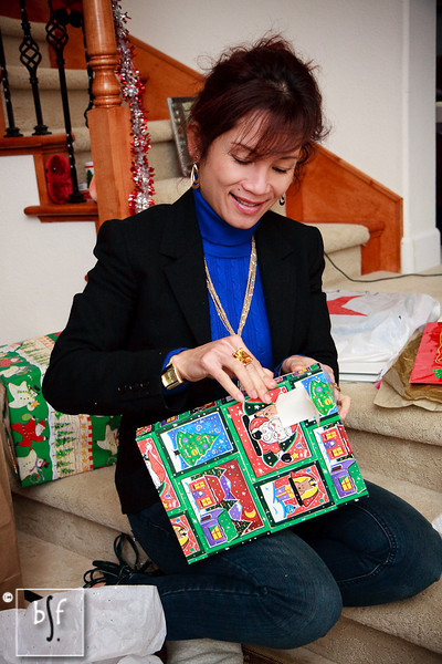 Dung carefully unwraps a Christmas gift.