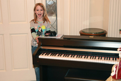 Reagan with her piano Dec. 24, 2010...virtuoso in the making?  She has been studying piano for a year and a half and doing well.