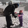 Opa brings a large piece of snow to start a snowman......