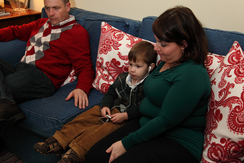 Caleb's sitting with his Aunt Cathy on the sofa with his Dad Ethan.