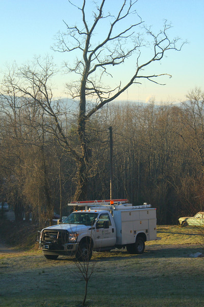"Christmas Day started with a power outage.  You can see the Duke lineman's ""hot stick"" poking above the truck as he attempts to thaw the thing out so that it will extend."