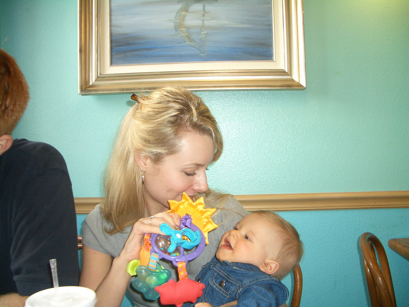 Stefanie plays with Cody while mommy eats.