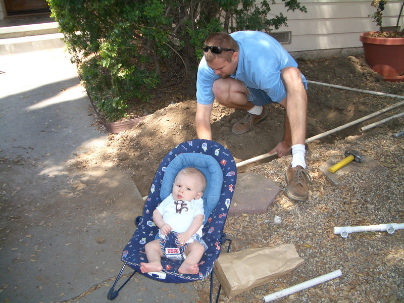 Daddy helping put sprinklers in the front yard. Cody helps by telling daddy what to do.