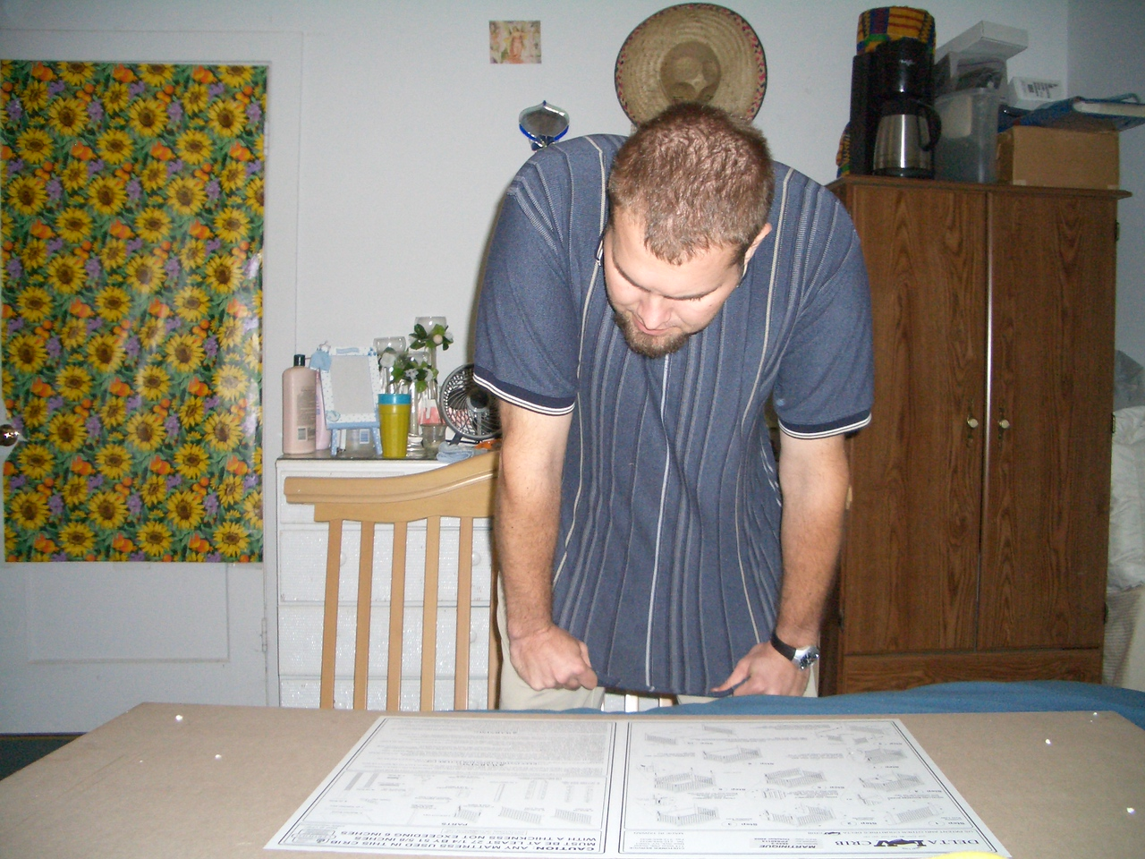 Daddy reading the directions on how to set up the crib. 10/4
