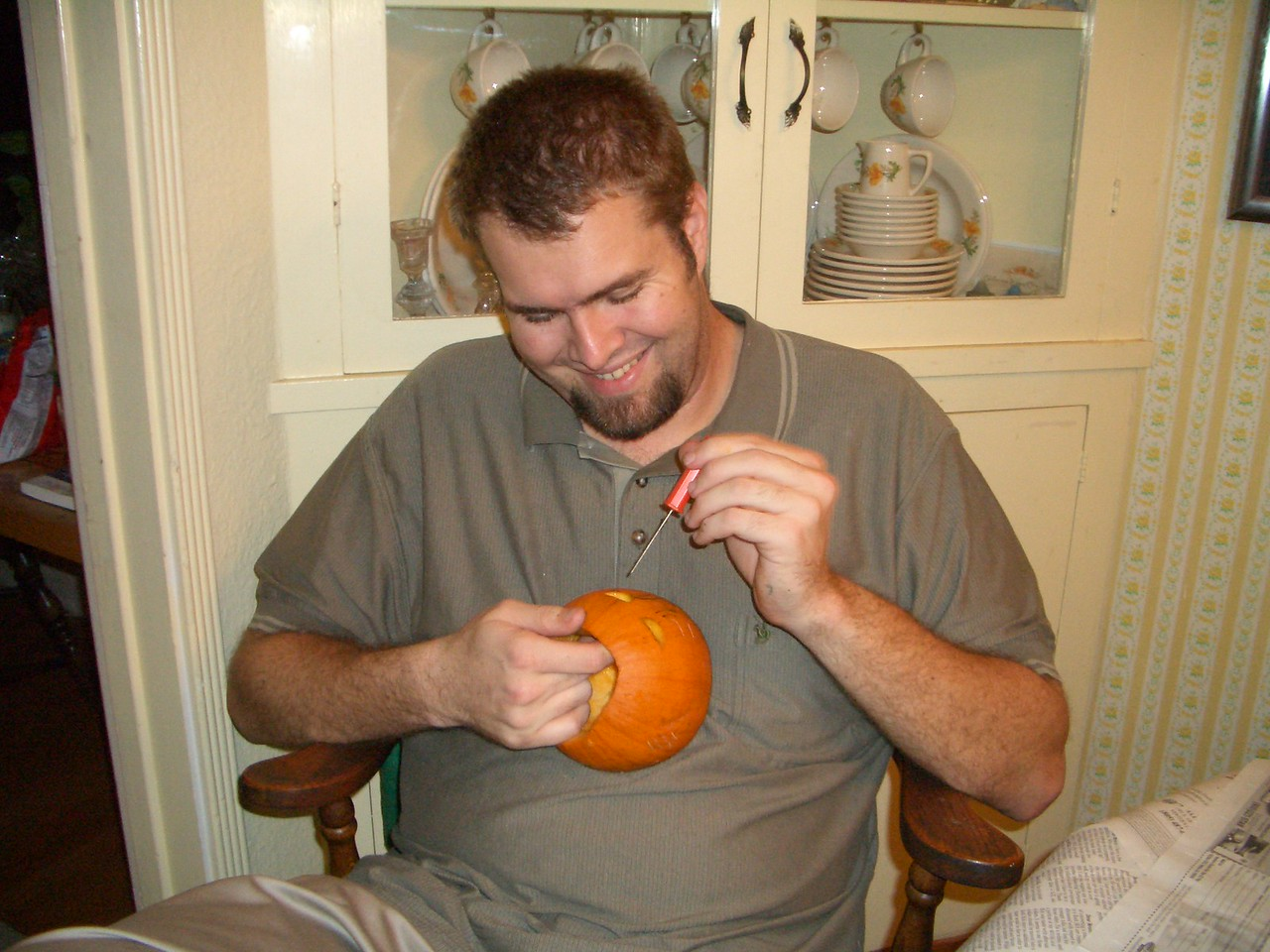 Daddy carving his little pumpkin.