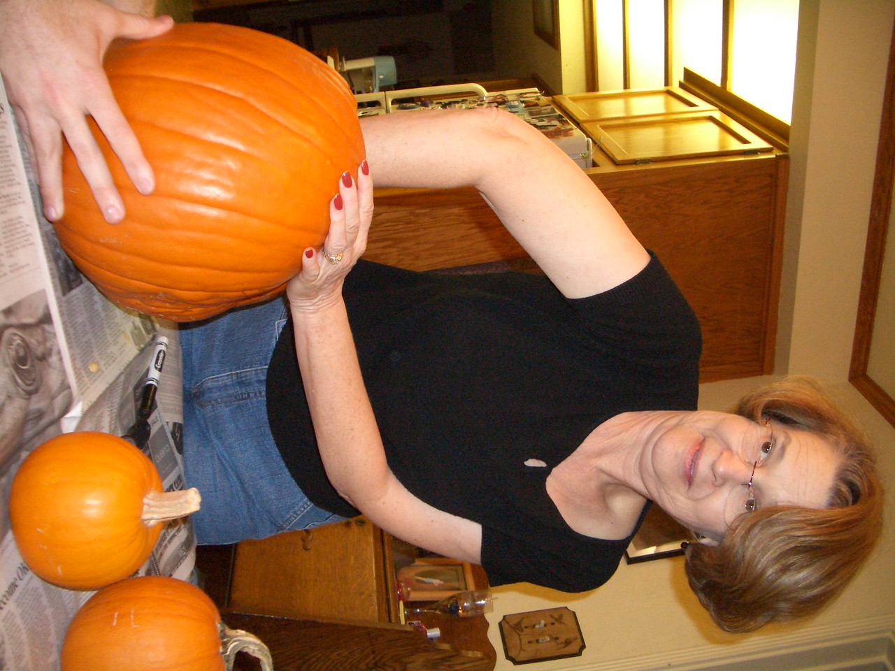 Grandma Jan uses a ice cream scoop to clean the pumpkin.