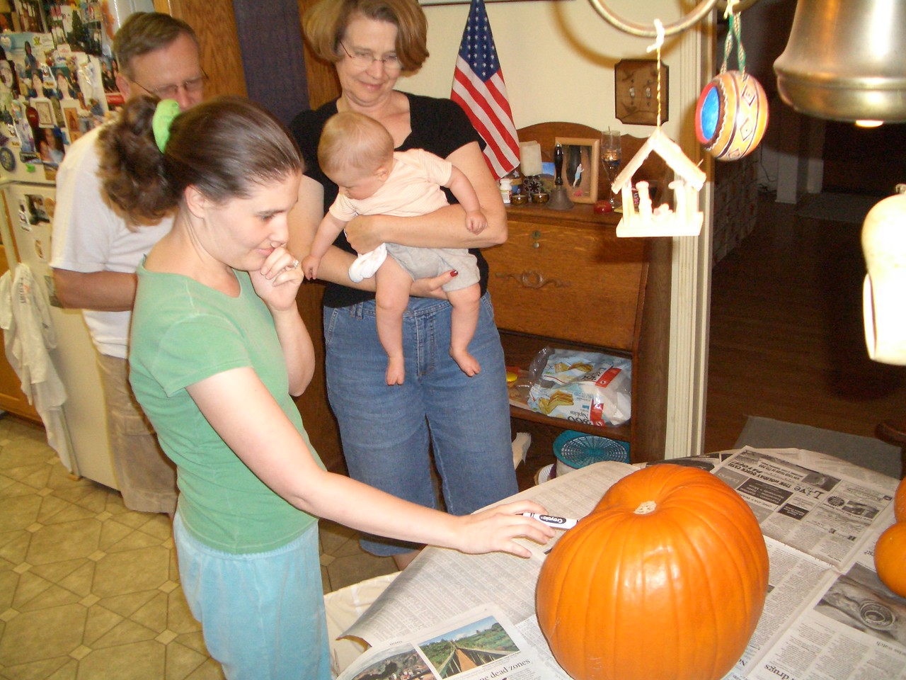 Mommy thinking about what kind of face to put on the pumpkin. 10/30/06