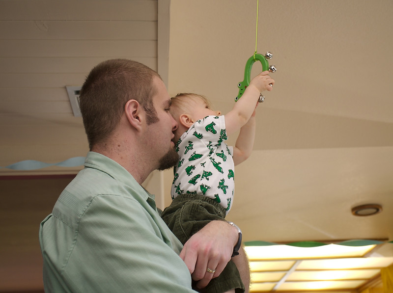 Cody reaching for one of the hanging frogs.