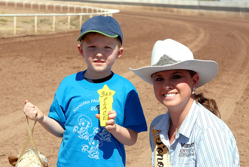 (5.6.2006 -- Sonoita, AZ)  Connor reaping the rewards of his 3rd place finish in the stick horse race at the Sonoita Horse races.