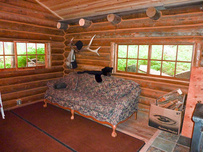 The lower log cabin living room had a comfortable couch and a very functional stove.