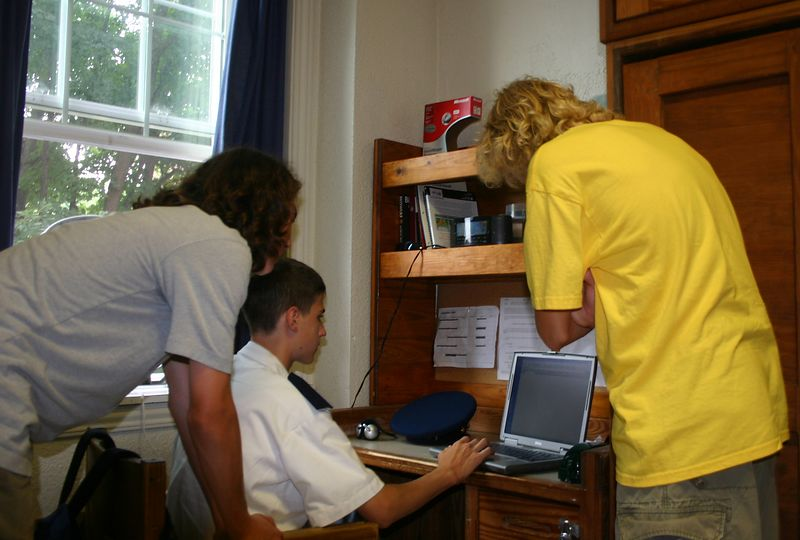 Patrick and Alex inspecting Evan's laptop.  Culver provides new Dell laptops to all incoming students.  The campus has a wireless network, so they can access important things like networked computer games from anywhere.