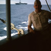 March 1965:  On board the USS Magoffin en route to Okinawa from Hawaii, Capt. Kenneth W. McCoy poses for the camera with the USS Valley Forge (LPH-8) visible in the background.  Capt. McCoy was an Air Liaison Officer attached to the 2nd Battalion 4th Marines.