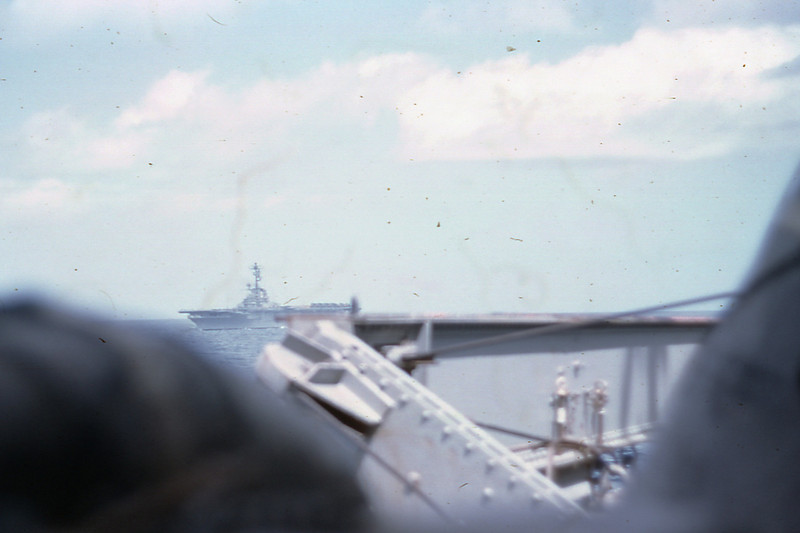 "March 1965:  Seen just off the Starboard side of the USS Magoffin (APA-199), the USS Valley Forge (LPH-8) is making the journey to Okinawa with the Magoffin as elements of Amphibious Squadron FIVE (PHIBRON 5).  The Happy Valley was transporting troops of the 1st Battalion 4th Marines, the UH-34D helicopters of HMM-161 ""Greyhawks"" as well as the A-4B Skyhawks of VMA-214 ""The Black Sheep.""  During it's time in Vietnam, HMM-161 became known as the ""Pineapple Squadron"" giving homage to its long history in Hawaii."