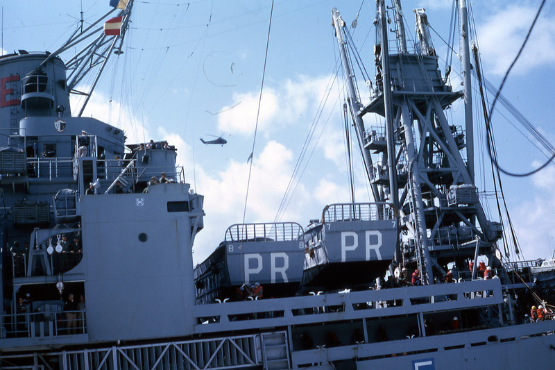 March 1965:  Operating side by side while en route to Okinawa, the USS Paul Reviere (APA-248) can be seen port side of the USS Magoffin (APA-199).  The two ships are cabling materials and personnel back and forth while UH-34D helicopters of HMM-161 operating from the deck of the USS Valley Forge (LPH-8) can be seen overhead.