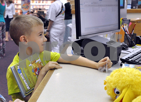 -Messenger photo by Joe Sutter<br /> <br /> Alix Lawler, 7, checks out three books (Bearenstein Bears, mostly) following Dan Wardell's storytime. Wardell told the kids to check out some books and read them, and to apply for a totally free library card if they didn't have one.