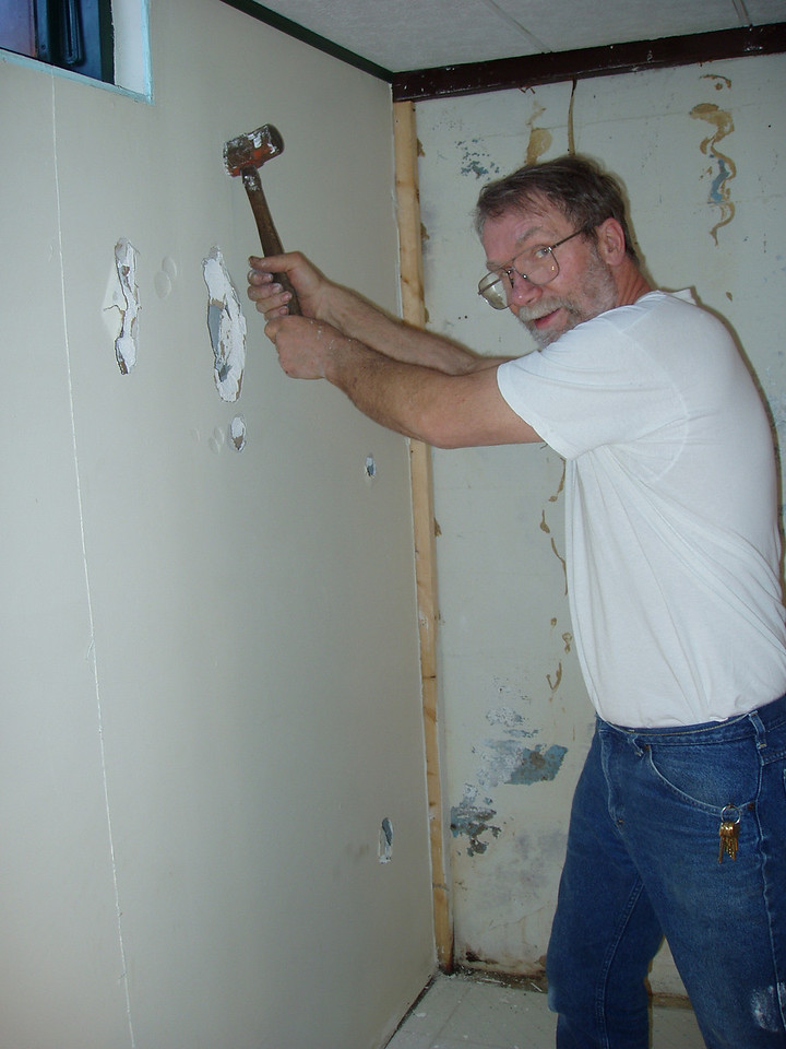 Daryl beating the sheet rock again.  Basement wall repairs.