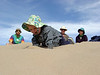 Denali learning about sand while Nathan, Chris and Frannie watch