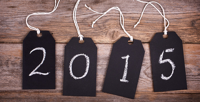 Chalkboard gift tags with strings, over old wood background, 2015 written in white chalk. New Year 2