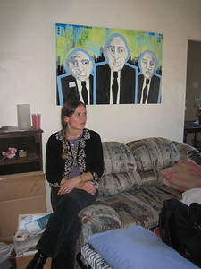 Djuna sits in her former apartment, now decorated with Abe's art (created by a friend of his),