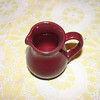 A small red pitcher presumably for milk or cream when serving coffee or tea.