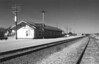 """LOMETA TRAIN DEPOT<br /> Lometa, Texas - 1970s<br /> <br /> Lometa's """"Standard No. 9"""" depot was built in 1911 and was a 24' X 160.5' wood frame building with drop siding, built to 1906 GC&SF standard depot blueprints. When first constructed, the depot had a """"White"""" waiting room on the eastern end, but that was later removed. <br /> <br /> This is what the depot looked like in its later years. You can see the bay window there by the pole for the signaling device. I took this during my black-and-white period on one of my trips to visit my grandfather."""