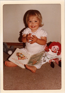 """Tonya playing """"patty cake"""" in reaction to the picture in the book. Nov 1973."""