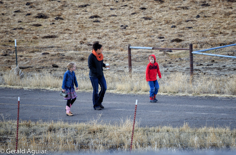 Abby, Amanda, and Kyle walking together on the road in front of Heather's home.