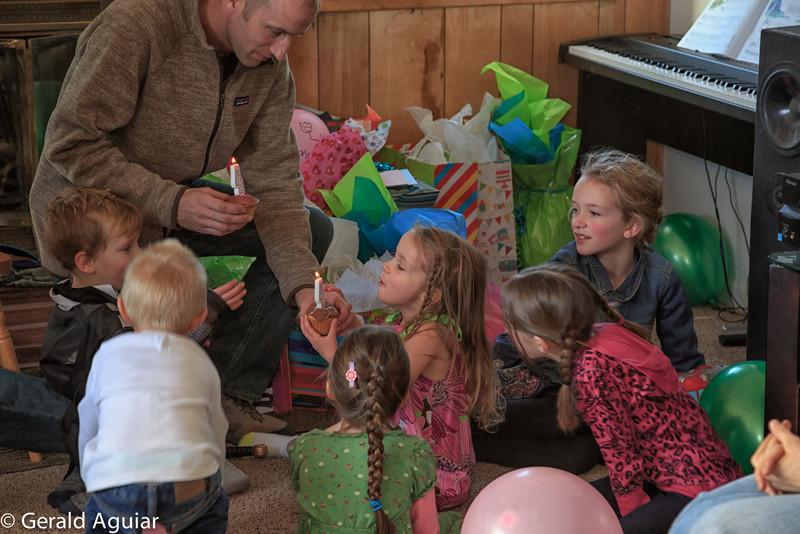 Caleb handing Ellie and Eli their birthday candles.