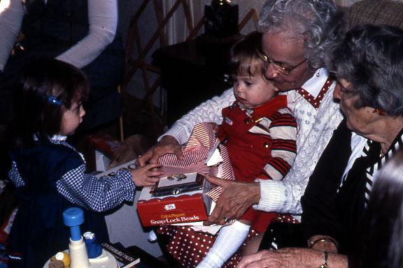 Grandma Marfione  is holding a baby, probably Mark. Margaret & Megan look on.