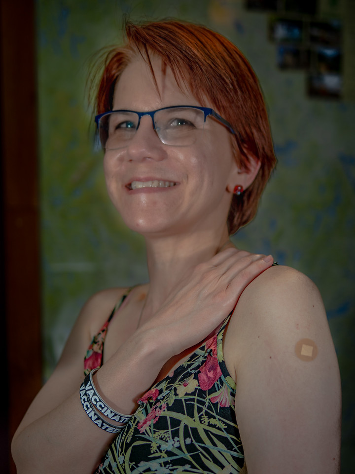 Cathy with band aid and vaccinated bracelet