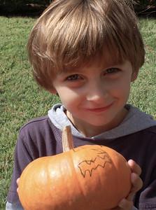 Patrick draws on a pumpkin