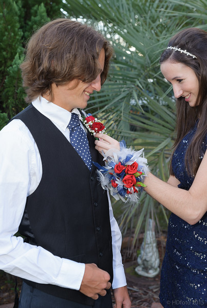 Its hard to pin the flower without stabbing him with the pin, but she did it.