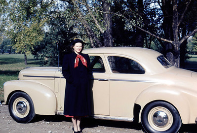 Older model Studebaker - as new cars were not readily available after the war. Note Dior look—longer skirts fashionable now that material was more available post-war. October 1948