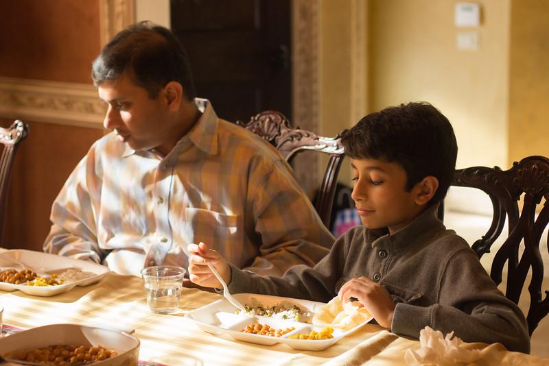 Bixby, OK: November 27, 2014: Shaurya Agarwal eats Thanksgiving lunch after prayer alongside his father Vishal Agarwal. Photo by: Kajal Sangal