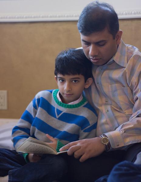 Bixby, OK: November 27, 2014: Vishal Agarwal reads an excerpt from the Ramayan during Thanksgiving prayer with his son Vaibhav Agarwal. Photo by: Kajal Sangal