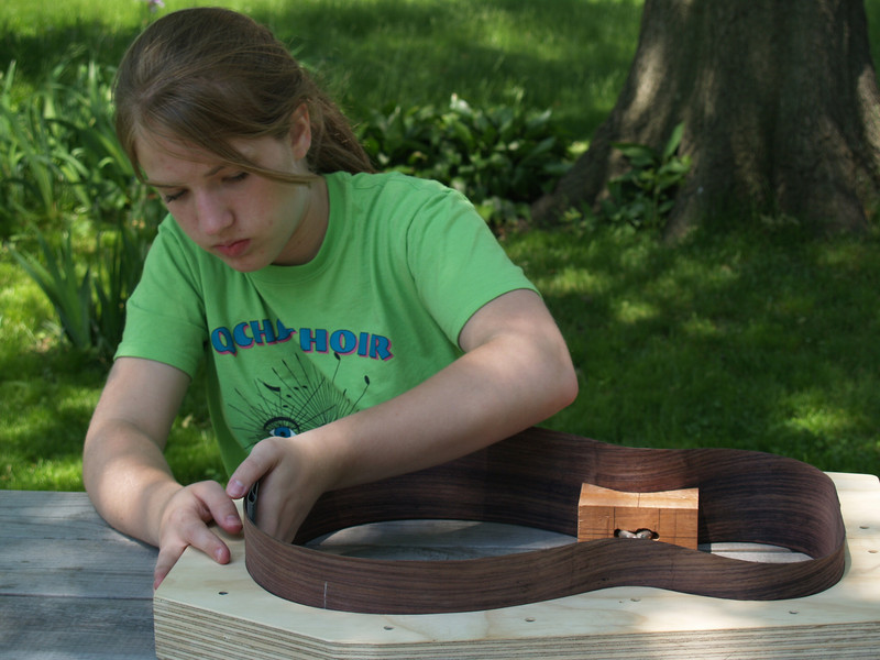 Lydia sanding walnut sides on the guitar she's building