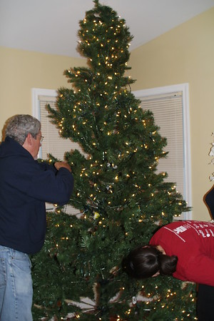helping fluff out the tree-  one section is burned out so we turned it to the back