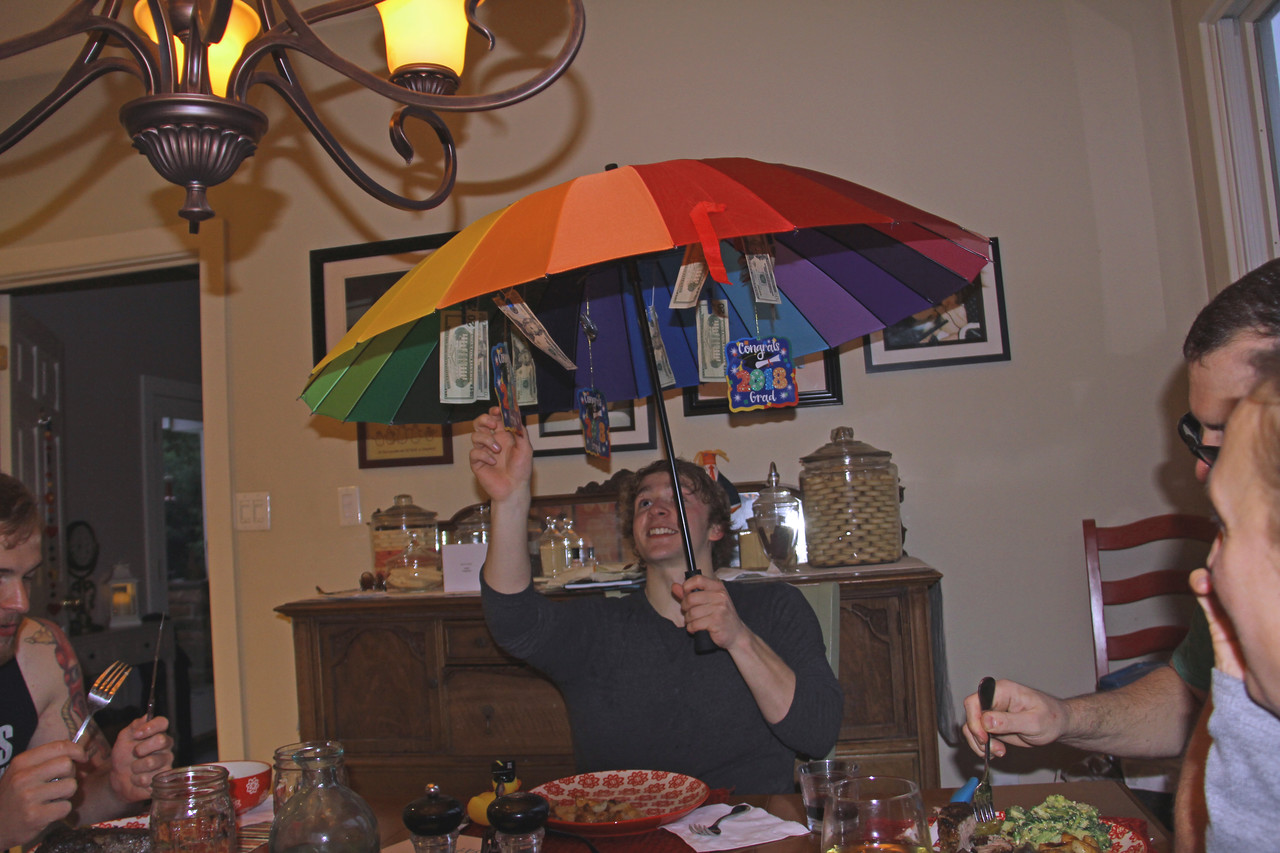 Wyatt opening the umbrella with his graduation gifts hanging.....