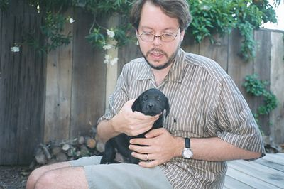 Mark holding Shasta as a puppy on back patio in Sacramento.  April 2000.