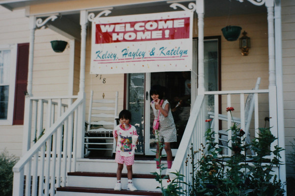 Girls on front porch with welcome home sign