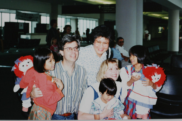 family at the airport picking up their adopted daughters from Vietnam