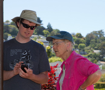 Cory shows Janet some features on his smartphone.