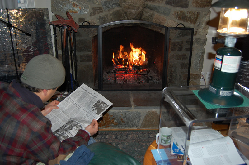 Camping indoors -- reading by propane lantern, warming by firewood.