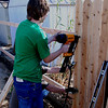 Brandon makes quick work of the fence boards with Craig's air nailer.
