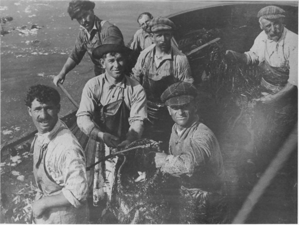 Photo Caption: Circa 1920s, Gaetano Giacalone (second from left, with apron and holding net) and his brother-in-law, Gaspare Giacalone (on his left, also holding net), along with fellow fishermen, fish for sardines off the coast of San Diego. Photo courtesy of Gaetano Giacalone.