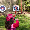 Anisa's arrow flies off.  You can see where it hit the screen to the left of the target.
